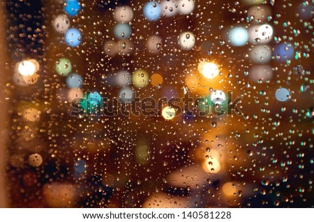 Drops of night rain on window, on back plan washed away lights of the torches. Shallow DOF - stock photo