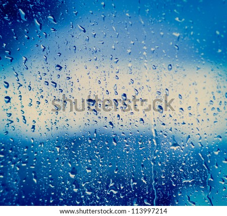 Drops of rain on blue glass background / drops on glass after rain - stock photo