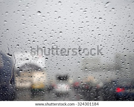 Drops of rain on car's mirror upon traffic jam.