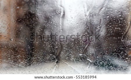 Drops Of Rain On Glass Background. Street Bokeh Lights Out Of Focus. Abstract Backdrop