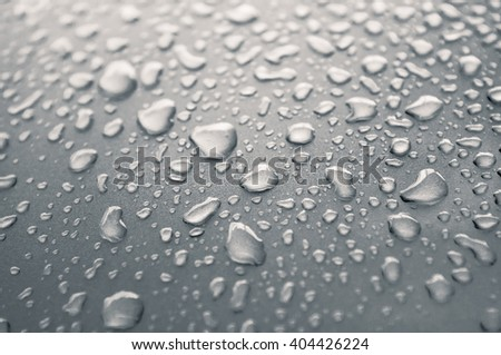 Drops of rain on metal background in monochrome.