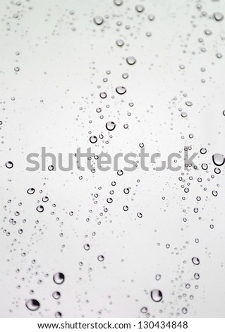 Drops of rain on the inclined window (glass). Shallow DOF. - stock photo