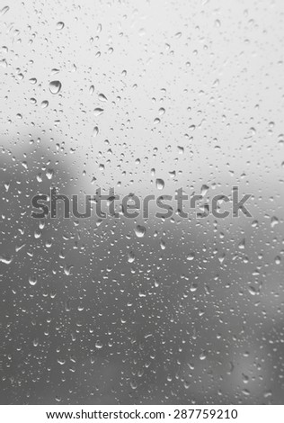 Drops of rain on the inclined window (glass). Shallow DOF - stock photo