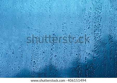 Drops of rain on window, blue background