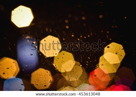 Drops of rain on window with abstract bokeh lights. - stock photo