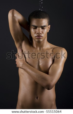 Drops of the water on naked body of a young man on black background. - stock photo