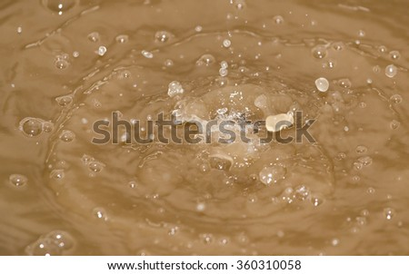 Drops of water falling into the dirty water