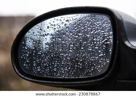 Drops of water on a car mirror.