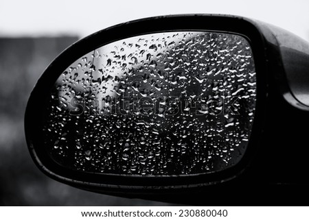 Drops of water on a car mirror. Black and white - stock photo