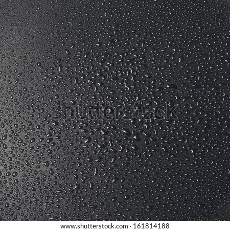Drops of water on a dark matte surface close up. - stock photo