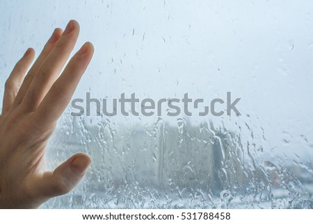 Drops of water on a glass and hand on window. Rain City background. white Texture