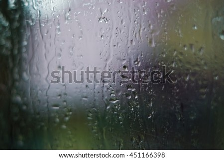 Drops of water on a window glass with a beautiful bokeh. Sunrise morning sky behind the window