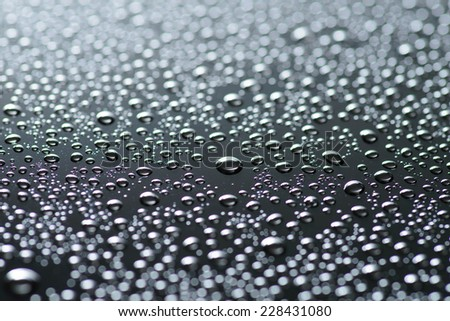 drops of water-repellent surface in black and white on a black background - stock photo