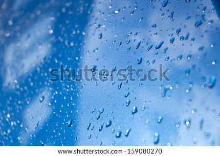 Drops on blue car mirror building with windows - stock photo