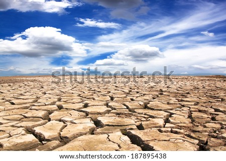Drought land against a blue sky with clouds - stock photo