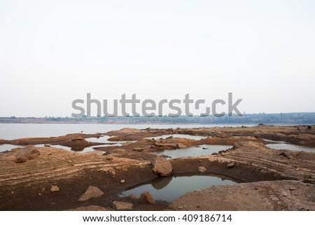 Drought the water in the dam reduced. Water basins and rock. - stock photo
