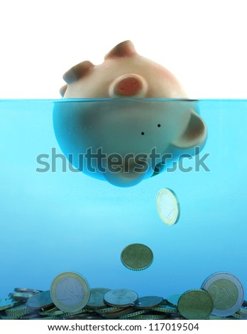Drowning in debt represented by a piggy bank sinking in blue water - stock photo