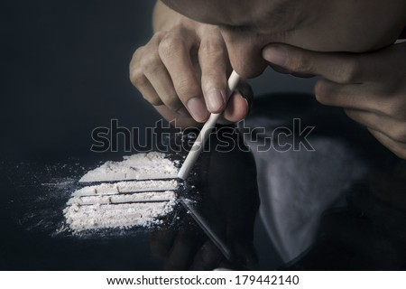 Drug abuse, man taking drugs, snorting cocaine portrait - stock photo