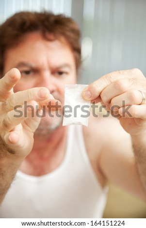 Drug addict holding a gram of cocaine.  **Dramatization - no illegal drugs were used in the making of this photograph** - stock photo