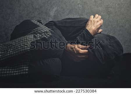 Drug Addict laying on the floor in agony, having an addiction crisis - stock photo
