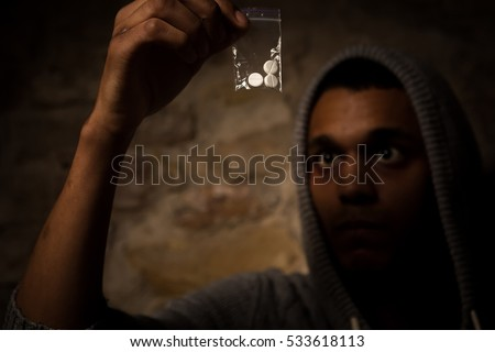 Drug addict man holding white powder in front of him. Man looking on drugs and showing it to camera.