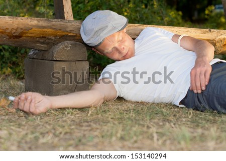 Drug addict passed out with a syringe in his hand next to a bench in the park - stock photo