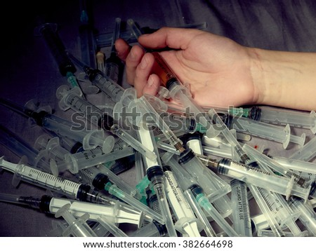 Drug addict. Photo a of human hand with syringe.