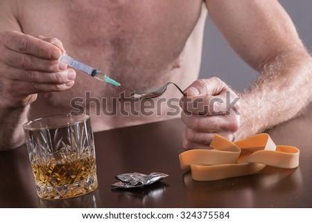 Drug addict preparing a dose of heroin - stock photo