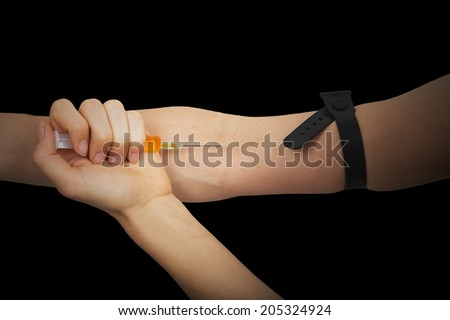 Drug addict pricking in the arm a drug with the syringe on black background - stock photo
