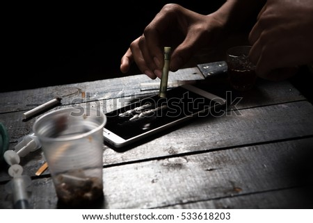 Drug addict using drugs with help of mobile or smart phone. Drug addict man alone. Disease concept. Drugs concept.