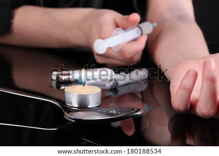 Drug addict with syringe in action on black background - stock photo