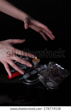 Drug addict with syringe on black background - stock photo