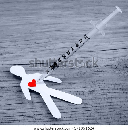 Drug Addiction Concept. Paper man with heart  and syringe on wooden background - stock photo