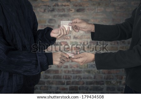 Drug dealer taking money for heroine - stock photo