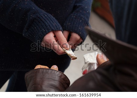 Drug dealer taking money for heroine and ecstasy - stock photo