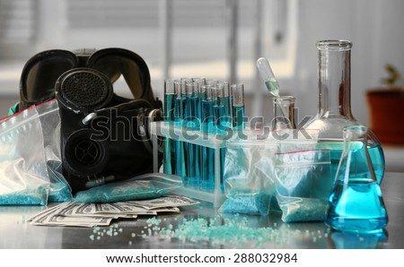 Drug laboratory: blue  methamphetamine and money on table close up - stock photo