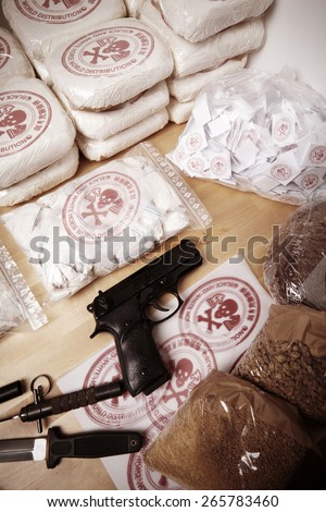 Drug packages, raw opium, drug dozens and weapons on table - stock photo