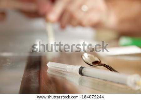 Drug paraphernalia, including a syringe and spoon, with a man snorting cocaine in the background.  Shallow depth of field for emphasis.   - stock photo