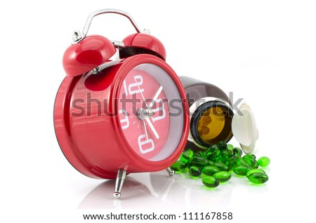 drug pill bottle and alarm clock,times to take care yourself - stock photo