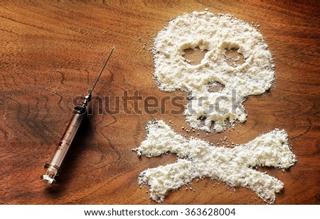Drug powder cocaine in the silhouette of the skull and syringe - stock photo