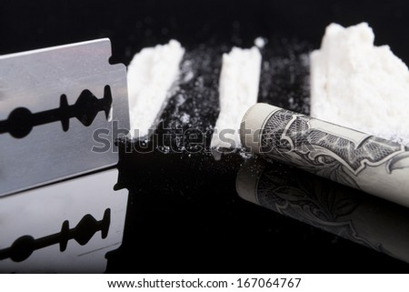 Drug rows with a dollar and razor blade on dark background with reflection