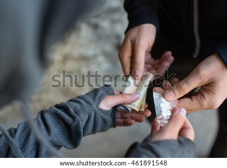 drug trafficking, crime, addiction and sale concept - close up of addict with money buying dose from dealer on street