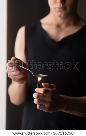 Drug use. Man cooking heroin using spoon - stock photo