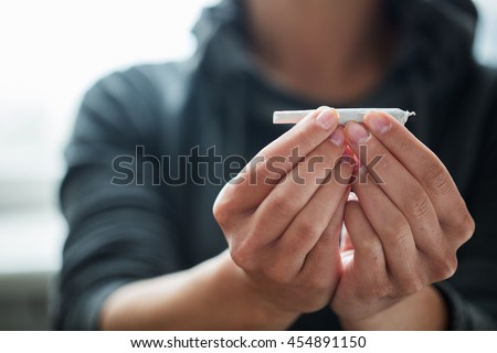 drug use, substance abuse, addiction and people concept - close up of addict hands with marijuana joint - stock photo