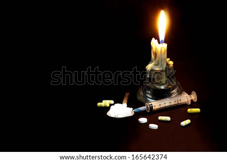 Drugs abuse and addiction concept. Candle, syringe, pill and spoon isolated black background. - stock photo