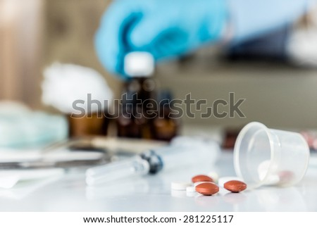 Drugs fall out from measuring cylinder with medical vials and syringes in the background.