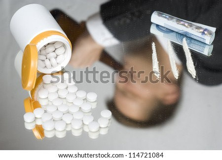 Drugs on a mirror. Out of focus reflection of a drinking businessman. - stock photo