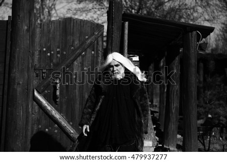 Druid old bearded man with long white hair and beard on serious face in fur coat sunny day outdoor on wood background, black and white