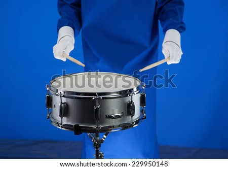 Drum and drumsticks in hand on blue background - stock photo