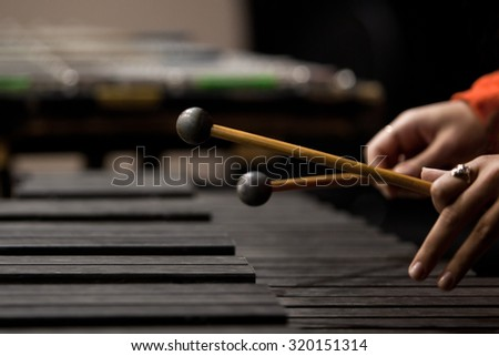 Drum sticks striking the xylophone in close up in dark colors - stock photo